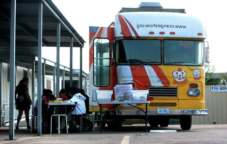 Students sit outside the Orange Show Art Bus as they learn art at Cage Elementary, Wednesday, Oct. 9, 2013, in Houston. A grant allowed the funding to convert a 1964 bus into a rolling classroom meant to offer art programs at schools where such have been curtailed or don't exist. Photo: Cody Duty, Houston Chronicle / © 2013 Houston Chronicle