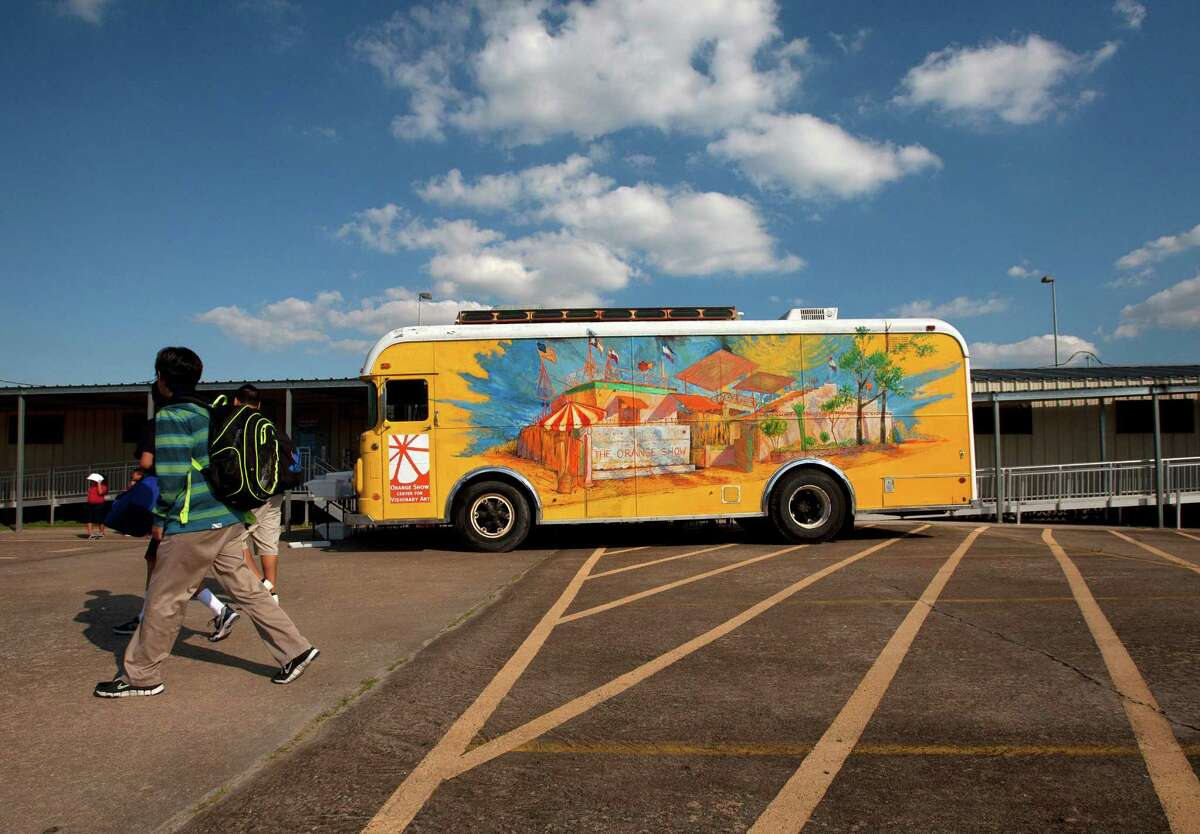 A student walks past the Orange Show Art Bus at Cage Elementary, Wednesday, Oct. 9, 2013, in Houston. A grant allowed the funding to convert a 1964 bus into a rolling classroom meant to offer art programs at schools where such have been curtailed or don't exist.