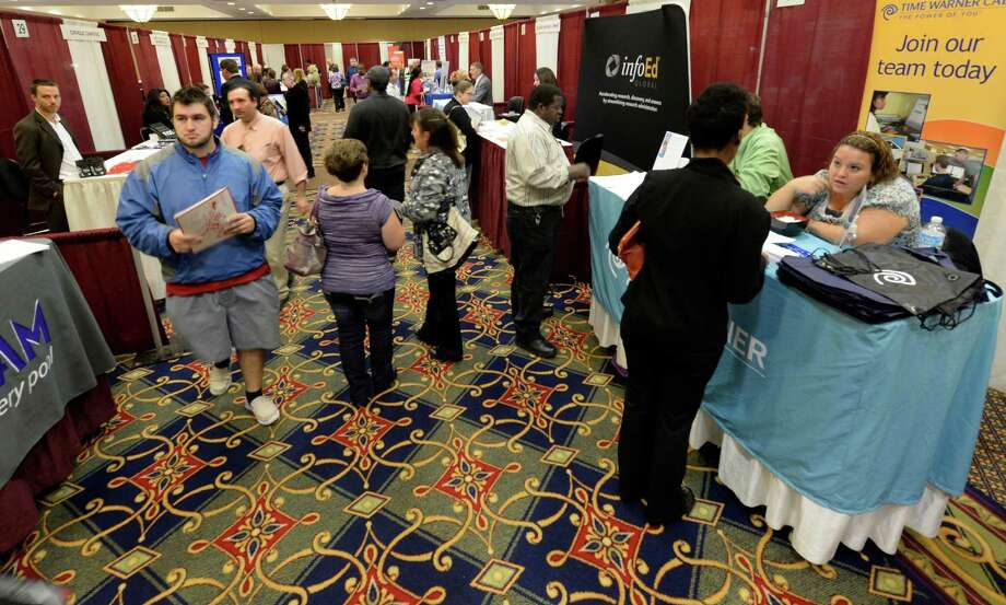 Job seekers look for employment opportunities during the Times Union Job Fair Monday morning, Oct. 14, 2013, at the Marriott on Wolf Road in Colonie, N.Y.  (Skip Dickstein/Times Union) Photo: SKIP DICKSTEIN / 00024247A