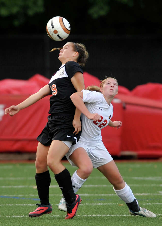 Ridgefield's Liane Keegans and Greenwich's Jessica Bartholomew compete for control of the ball during their game at Greenwich High School in Greenwich, Conn., on Monday, Oct. 14, 2013. The game ended in a 1-1 tie. Photo: Jason Rearick / Stamford Advocate