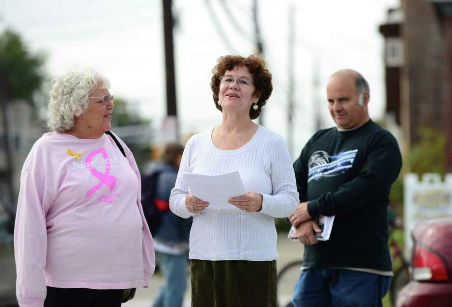 Green Party Albany mayoral candidate Theresa Portelli, center, announced her economic agenda for the city of Albany Monday morning, Oct. 14, 2013, outside the Honest Weight Food Co-op in Albany, N.Y. The economic plan includes switching to a land value tax to help spur development of Albany?s abandoned building, and investment in local worker-owned co-ops. It also calls for a local income tax, and to curtail Albany?s landfill revenue loss by becoming a zero-waste city. (Will Waldron/Times Union) Photo: WW