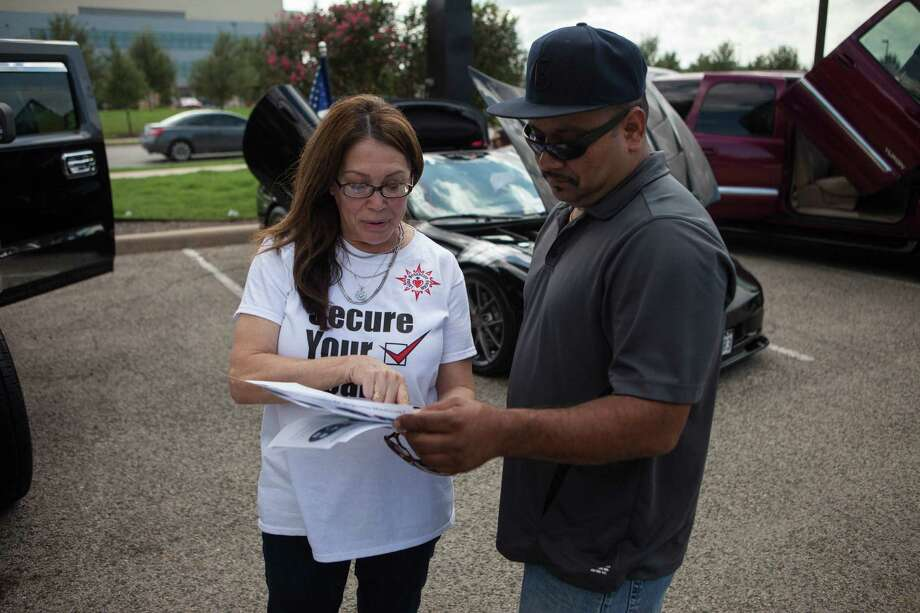 Jill Ramirez (left), the director of outreach for the Latino Healthcare Forum, passes out fliers and explains components of the Affordable Care Act to Ernest Garcia recently in Austin. Photo: Spencer Selvidge / Texas Tribune