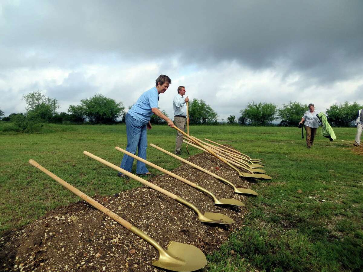 New Braunfels Mayor Gale Pospisil grabs a shovel for the ceremonial groundbreaking ceremony Monday, Oct. 14, 2013, for Fischer Park, the city's first major park east of Interstate 35. Heavy rains stopped just before the ceremony for the 62-acre park that will open in one year.