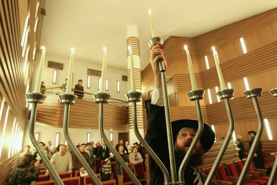 BERLIN, GERMANY - DECEMBER 06:  Rabbi Yehuda Teichtal lights a menorah on the sixth day of Hanukkah at the Orthodox synagogue at the Chabad-Lubavitch Jewish Education Center on December 6, 2010 in Berlin, Germany. Congregation members met in a speical prayer service for the victims of the Carmel fire in Israel, which has killed at least 41 people.  (Photo by Sean Gallup/Getty Images) Photo: Sean Gallup / 2010 Getty Images