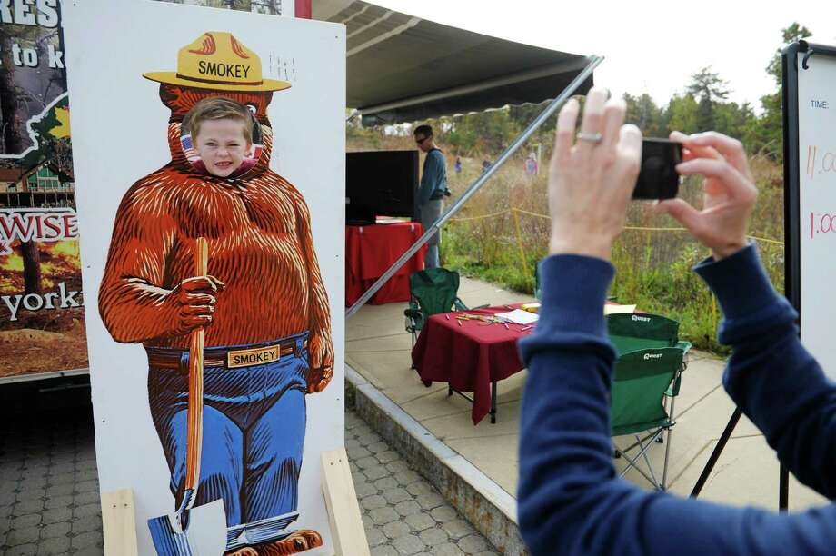 Jonathan Forster, 5, from Malta gets his photograph taken by his mom, Heather Forster Monday, Oct. 14, 2013, at the Albany Pine Bush Discovery Center in Albany, N.Y.  Smokey Bear was on hand at the event to teach children about wildfire prevention and the use of prescribed fire as an important management tool in the Pine Bush Preserve.   (Paul Buckowski / Times Union) Photo: Paul Buckowski / 00024167A