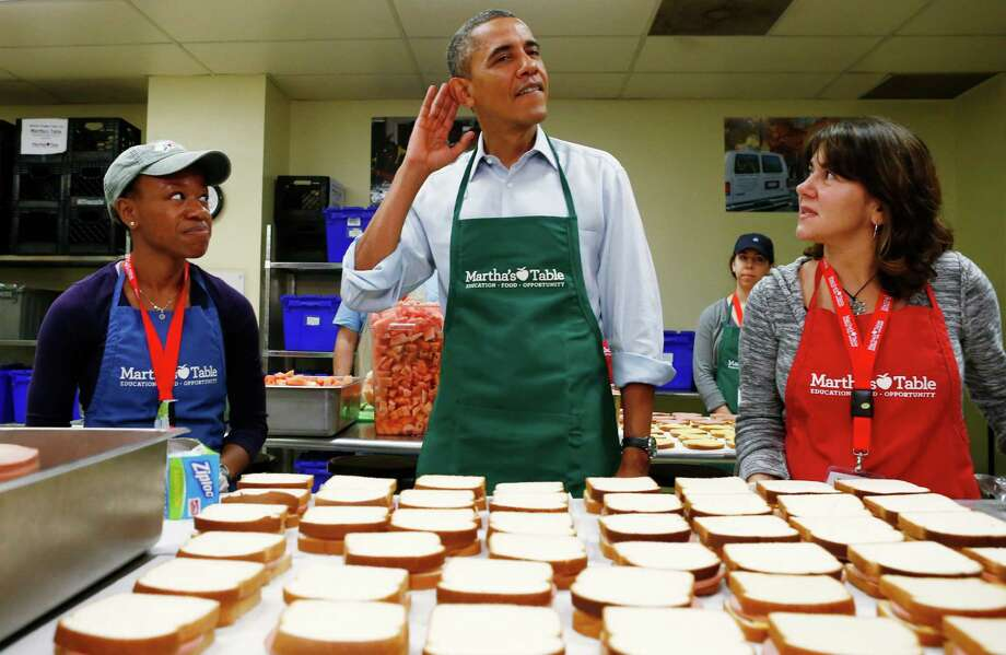"President Barack Obama cups his ear as he stands between two volunteers during a visit to Martha's Table, which prepares meals for the poor and where furloughed federal employees are volunteering, in Washington, Monday, Oct. 14, 2013. Speaking there Obama said that if Republicans can't resolve the standoff over the debt ceiling and the partial government shutdown, quote, ""we stand a good chance of defaulting."" (AP Photo/Charles Dharapak) ORG XMIT: WHCD103 Photo: Charles Dharapak / AP"