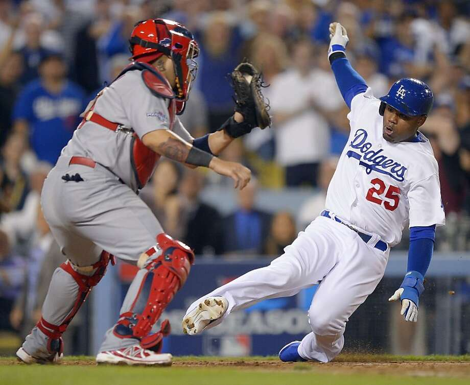 Dodgers outfielder Carl Crawford begins his slide into home plate in the eighth inning. Umpire Mike Everitt ruled that he narrowly beat the tag of Cardinals catcher Yadier Molina. Photo: Mark J. Terrill, Associated Press