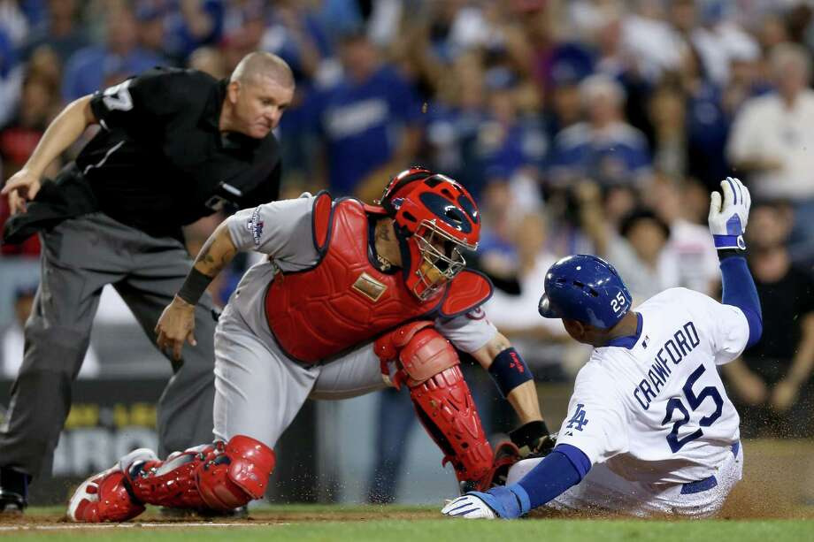 The Dodgers' Carl Crawford slides safely under Yadier Molina's tag to score during the eighth inning of Game 3 on Monday in Los Angeles. Crawford scored from second base on a one-out single. Photo: Jeff Gross / Getty Images