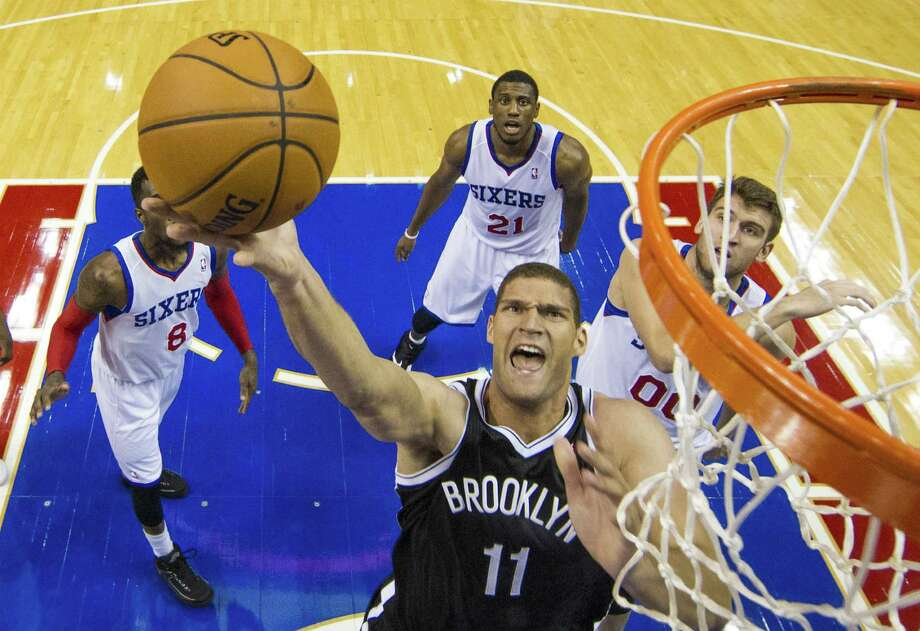 Brooklyn center Brook Lopez lays the ball up as Philadelphia's Tony Wroten (left), Thaddeus Young (center) and Spencer Hawes look on. Photo: Chris Szagola / Associated Press