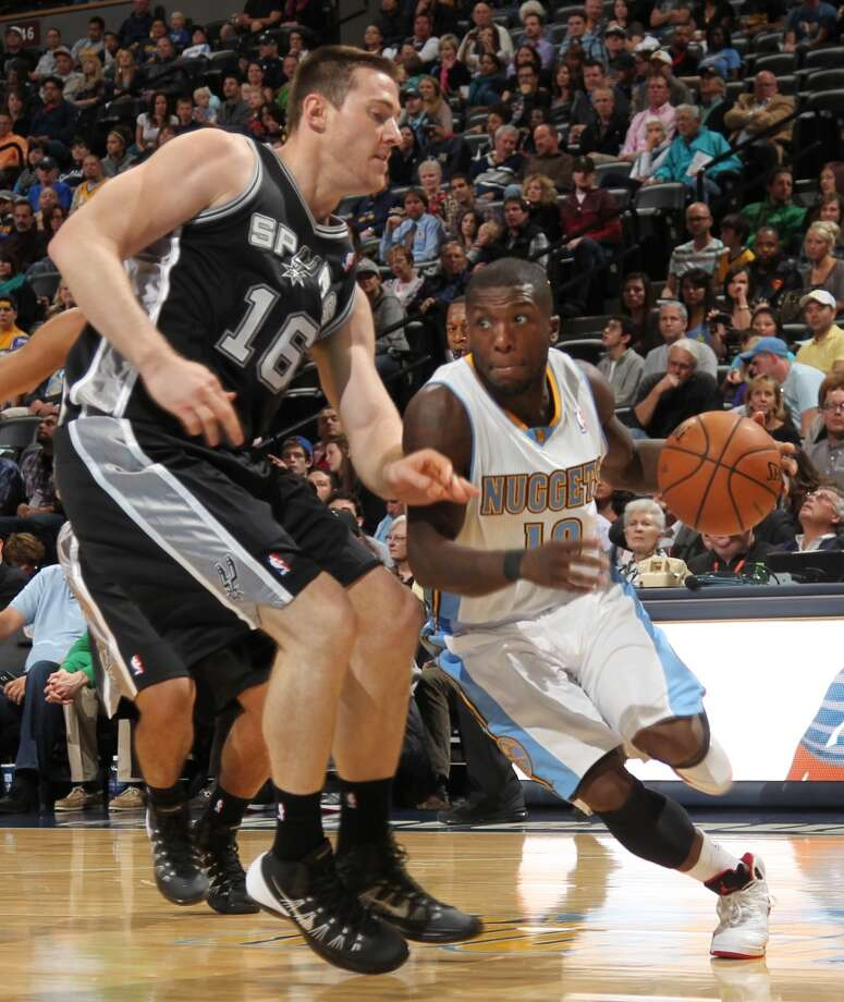 Denver Nuggets guard Nate Robinson, right, works ball inside as San Antonio Spurs forward Aron Baynes covers in the first quarter of an NBA preseason basketball game in Denver on Monday, Oct. 14, 2013. (AP Photo/David Zalubowski) Photo: Associated Press