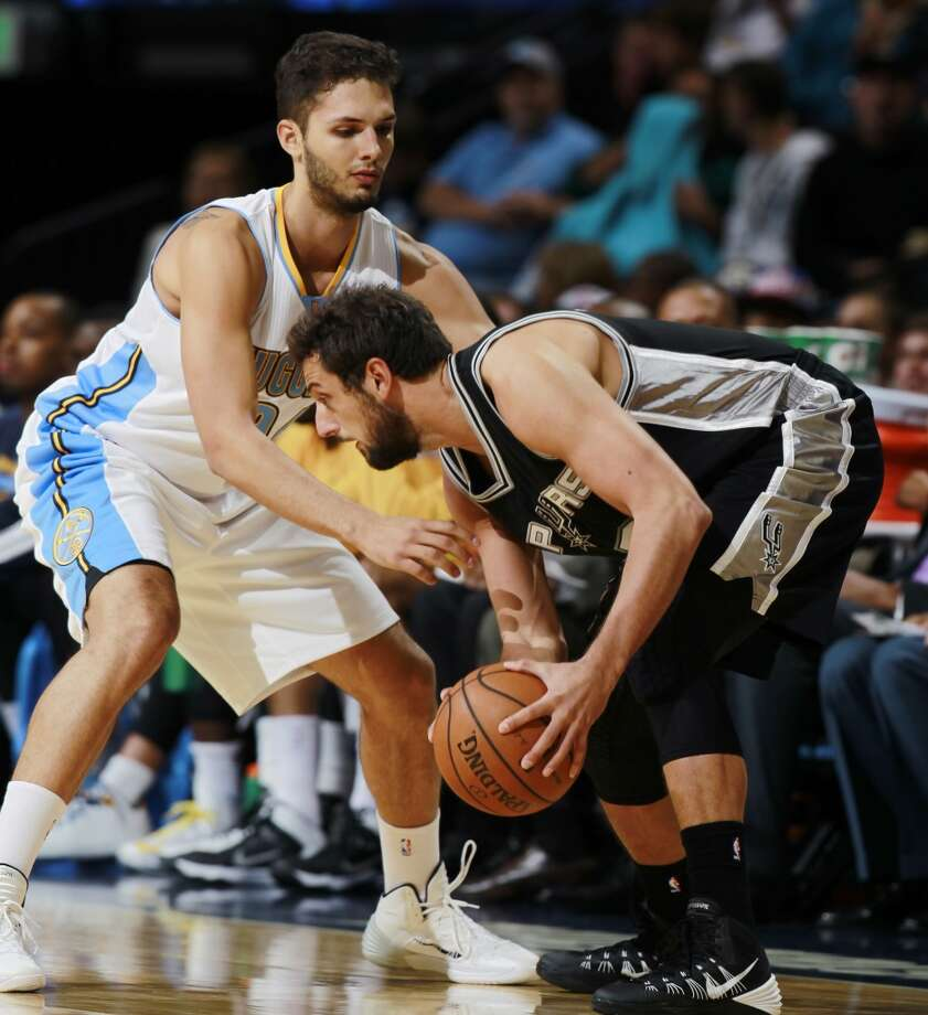 San Antonio Spurs guard Marco Belinelli, right, of Italy, works ball inside against Denver Nuggets guard Evan Fournier, of France, in the first quarter of an NBA preseason basketball game in Denver on Monday, Oct. 14, 2013. (AP Photo/David Zalubowski) Photo: Associated Press