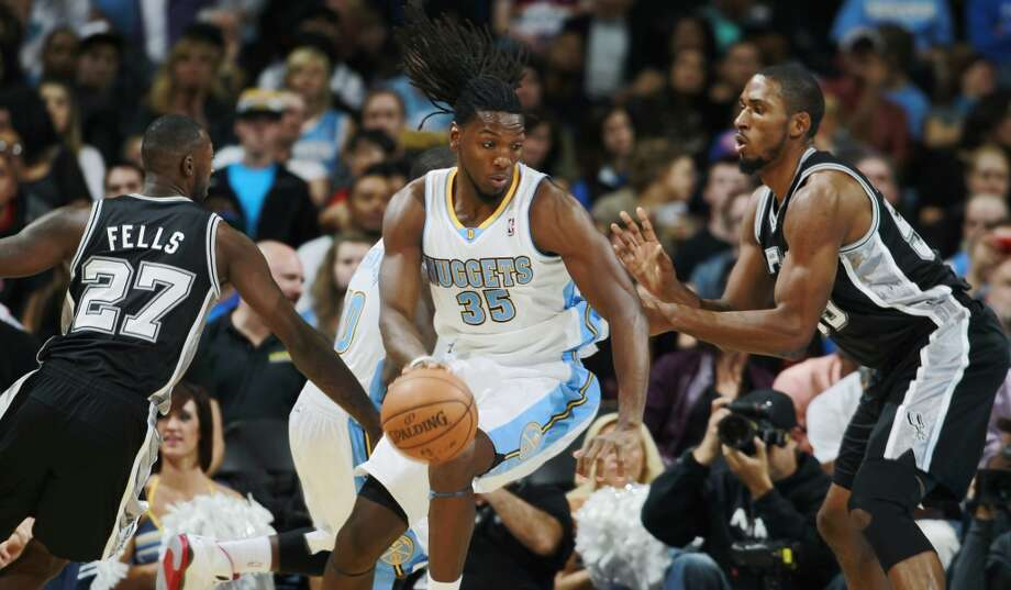 Denver Nuggets forward Kenneth Faried, center, drives the lane for a shot as San Antonio Spurs forward Courtney Fells, left, and center Marcus Cousins cover in the fourth quarter of the Nuggets' 98-94 victory in an NBA preseason basketball game in Denver on Monday, Oct. 14, 2013. (AP Photo/David Zalubowski) Photo: Associated Press