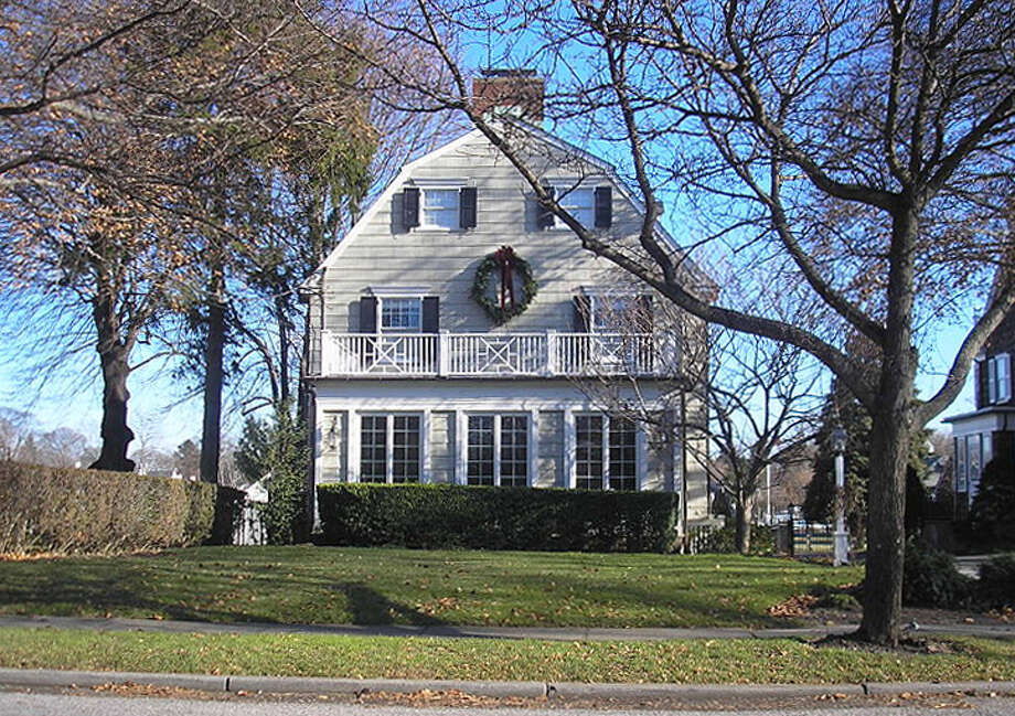 "Amityville House, real life scene of  gruesome murder in which Ronald De Feo massacred 6 of his family members. Later, the Lutz family moved in, and then moved out, chased, they claimed, by unwelcoming paranormal activity exhorting them (famously) to ""Get Out!"" Photo: Seulatr Via Wiki Commons"