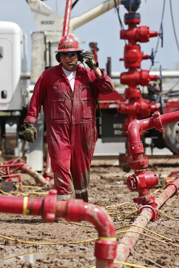 A worker walks away from a wellhead with a frac tree, background, at a ranch southwest of Ben Bolt, Texas. The well, located near the Jim Wells and Duvall County line, was drilled to a depth of over one mile. Photo: Jerry Lara, San Antonio Express-News