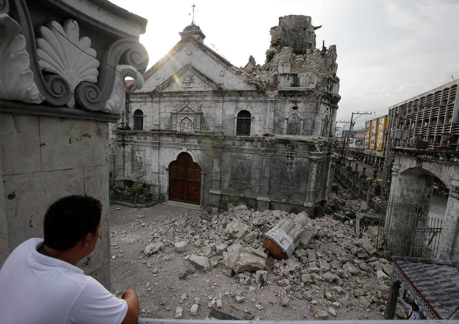 A resident looks at the rubble following a 7.2-magnitude earthquake that hit Cebu city in central Philippines and toppled the bell tower of the Philippines' oldest church Tuesday, Oct. 15, 2013. The tremor collapsed buildings, cracked roads and toppled the bell tower of the Philippines' oldest church Tuesday morning, causing multiple deaths across the central region and sending terrified residents into deadly stampedes. (AP Photo/Bullit Marquez) Photo: Bullit Marquez, ASSOCIATED PRESS / AP2013