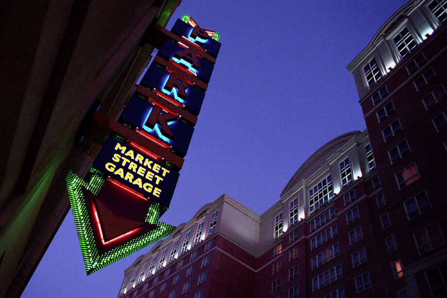 Green neon glows through perforated metal arrow outlining the sign for the Market Street Garage, across the street from the Westin Riverwalk Hotel.  Photo: MIKE GREENBERG, SAN ANTONIO EXPRESS-NEWS / SAN ANTONIO EXPRESS-NEWS