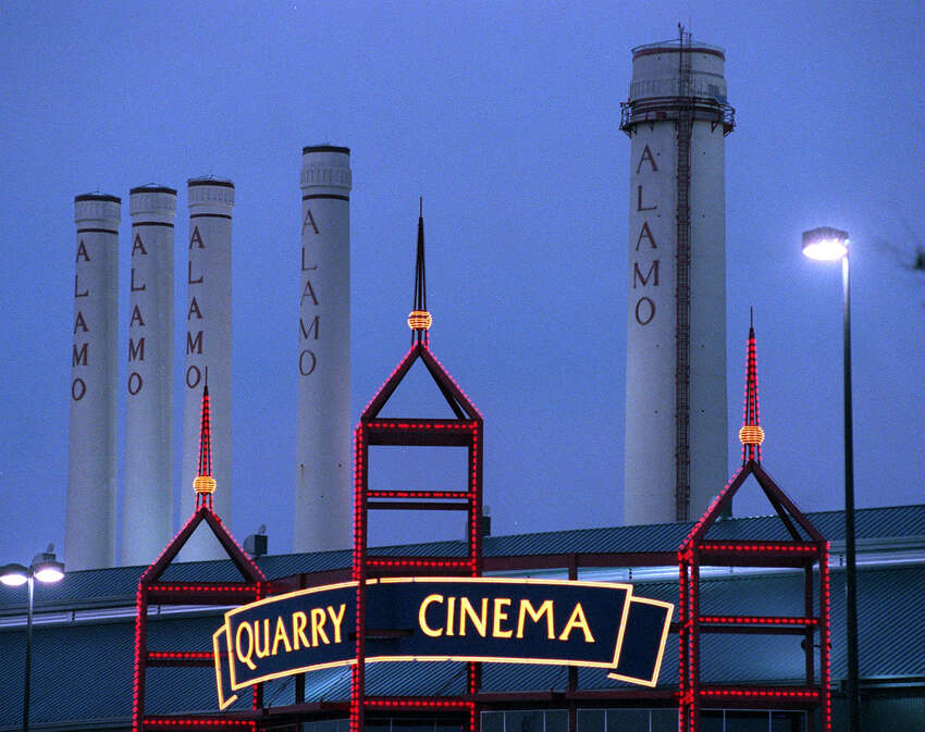 The Quarry Cinema with its neon lights contrast the historical old Alamo Cement smokestacks located in the Quarry Market.