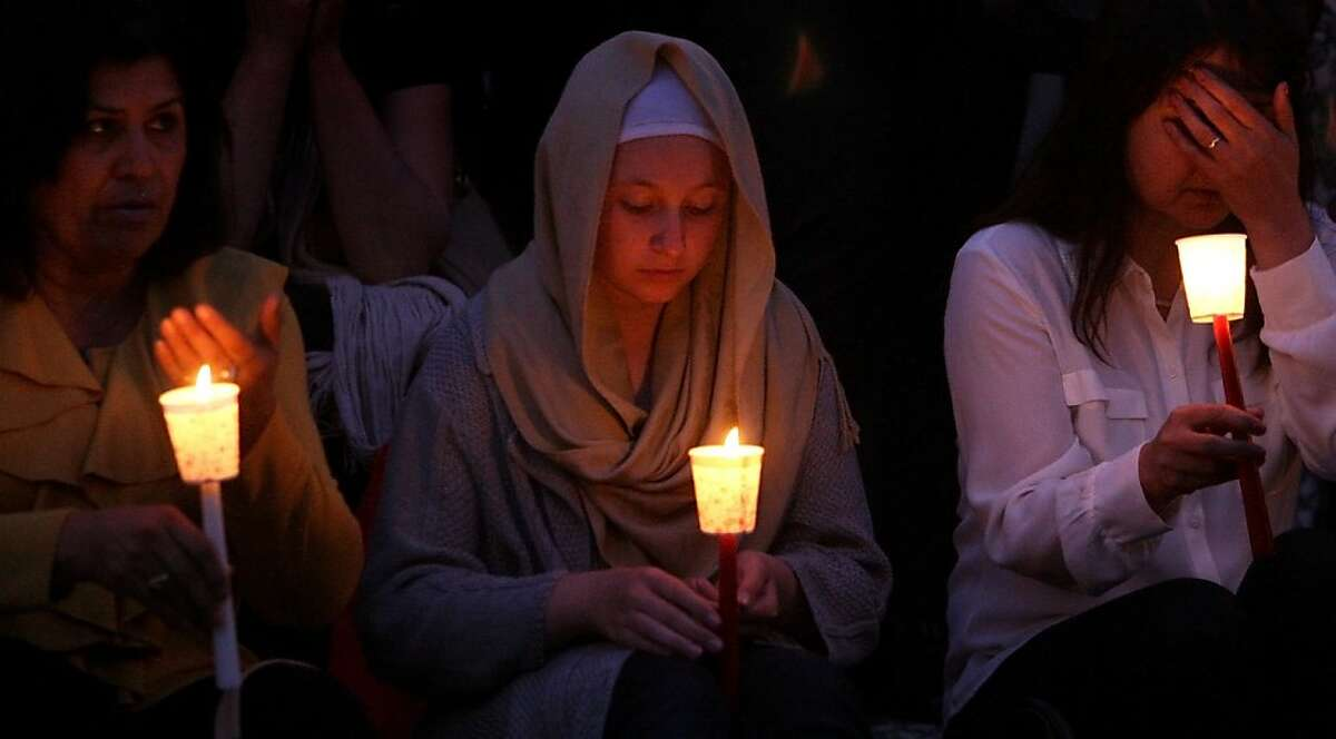 Zakia Amiri, left, and Fatima Mohammadi, center, pray during the candle light vigil that followed the 5000 Open Wounds event at the Cal State East Bay campus, in Hayward, Calif. on Sunday, Oct. 13, 2013.