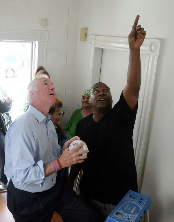 Fred Reynolds shows Bridgeport Mayor Bill Finch where to install the smoke detector in a home at 279 Brooks Street, the city's 40,000th smoke alarm installation, Tuesday, Oct. 15, 2013.  The Bridgeport Fire Department is unique in that they not only give out free smoke detectors but also install the units throughout the city. Photo: Autumn Driscoll / Connecticut Post