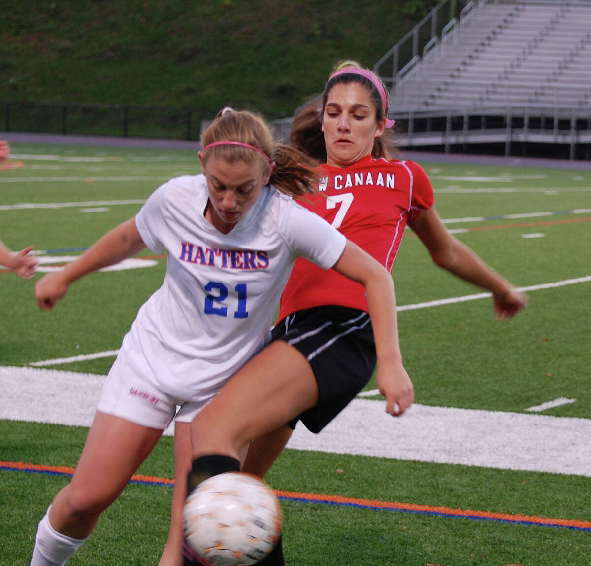 New Canaan's Azada Amis-Aslani (No. 7) and Danbury's Charlotte Blain (No. 21) get tangled up going for the ball during Danburyís 2-1 win at Danbury High School on Monday, Oct. 14, 2013. Contributed photo by Kim Persky.