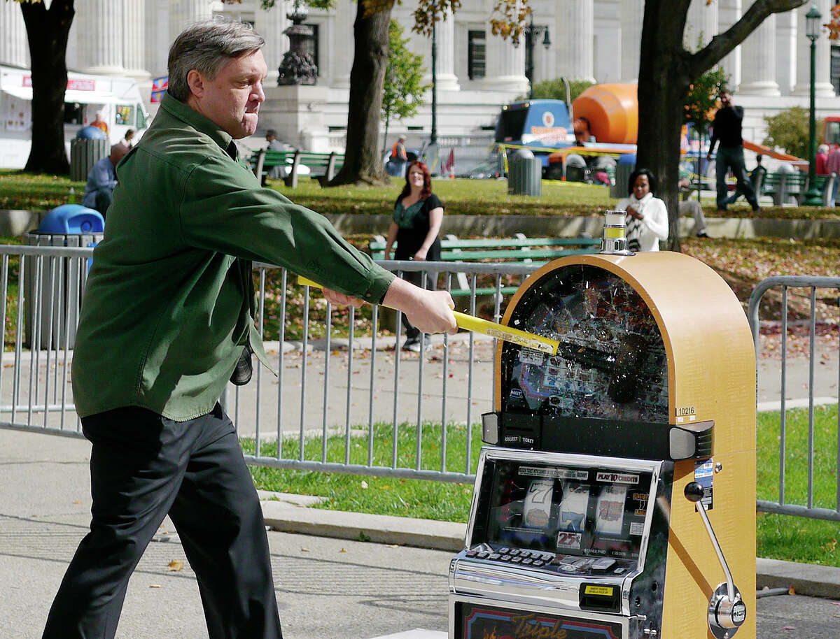 David Blankenhorn, president of the Institute for American Values, uses a sledge hammer to strike a slot machine during an event put on by the institute in West Capitol Park on Tuesday, Oct. 15, 2013 in Albany, NY. Participants taking part in the event took turns using a sledge hammer to hit a slot machine. (Paul Buckowski / Times Union)