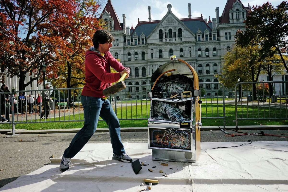 Bill Sisk, a research assistant with the Rockefeller Institute of Government, uses a sledge hammer to strike a slot machine during an event put on by the Institute for American Values in West Capitol Park on Tuesday, Oct. 15, 2013 in Albany, NY. Participants taking part in the event took turns using a sledge hammer to hit a slot machine. (Paul Buckowski / Times Union)