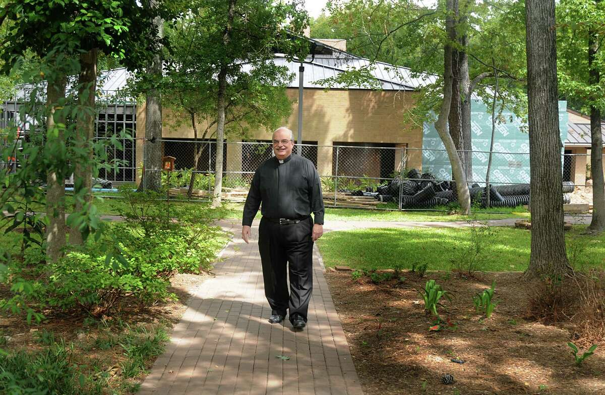 Father Pat Garrett walks in the courtyard, as construction on the Parish, in background, continues, at Sts. Simon and Jude Catholic Parish, 26777 Glen Loch Drive. Renovation on the Parish is almost complete. Photo by David Hopper