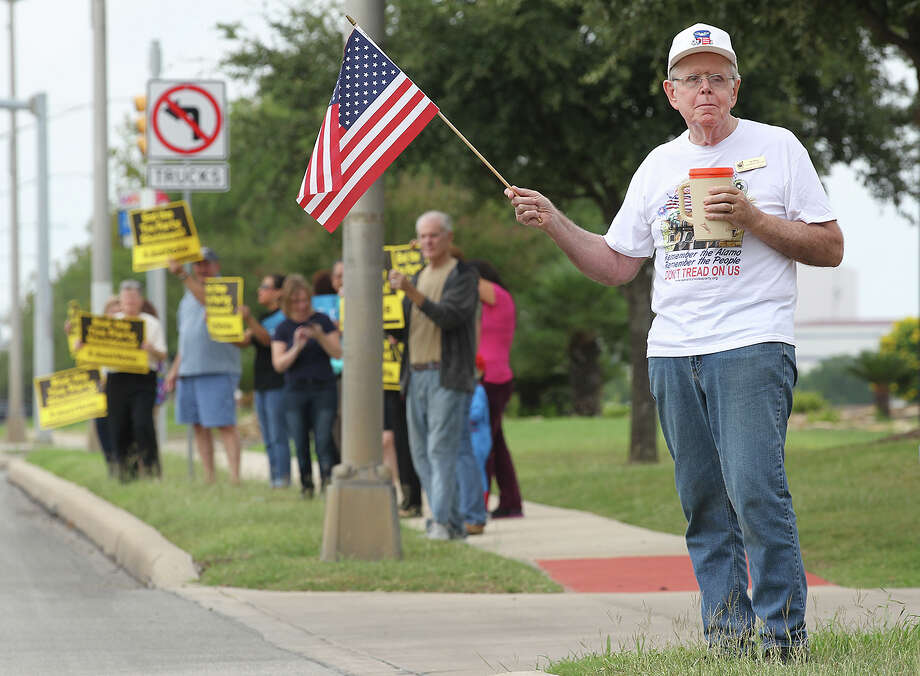 San Antonio Tea Party member Joe Bissett shows his support for  U.S. Sen. Ted Cruz as protesters, in back, gather in front of the senator's offices at Port San Antonio, Tuesday, Oct. 15, 2013. Cruz is seen at the heart of the government shutdown. A small group of pro and anti Cruz gather at the site late Tuesday morning. Photo: JERRY LARA, San Antonio Express-News / © 2013 San Antonio Express-News