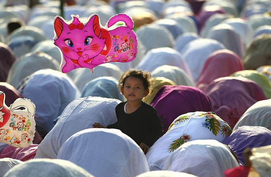 Hover cat:A girl holds her kitty balloon as Muslims pray on Eid al-Adha in Jakarta. Traditionally Muslims all over the 