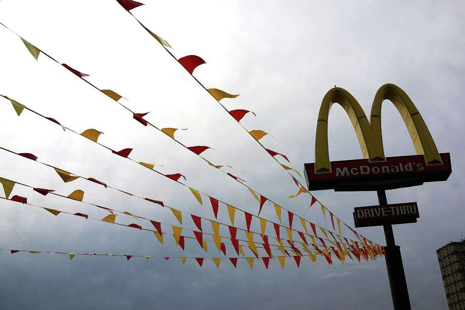 Flags fly in a McDonald's parking lot on August 23, 2013 in the Brooklyn borough of New York City. McDonald's announced that in November, it will give away 20 million books featuring storylines pushing healthy nutritional messages with Happy Meals. Photo: Spencer Platt, Getty Images / 2013 Getty Images