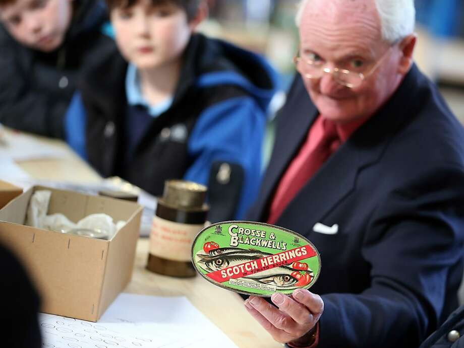 Canned herring saved my life: In Bristol, England, David Isherwood shows schoolchildren a replica tin from a Red Cross parcel similar to the ones he received as a boy. The 80-year-old Channel Islands resident - who as a survivor of the German occupation during World War II was kept alive by food parcels he received - traveled to the Red Cross Bristol Emergency Response Unit to celebrate the 25 million food parcels issued worldwide by the British Red Cross. Photo: Matt Cardy, Getty Images
