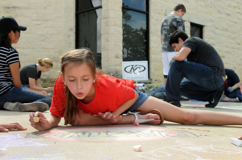 Kylie Young, 10, a pupil at Northland Christian School, works on her chalk art creation during CreekFest on Saturday, Oct. 12. Photo: Jerry Baker, Freelance