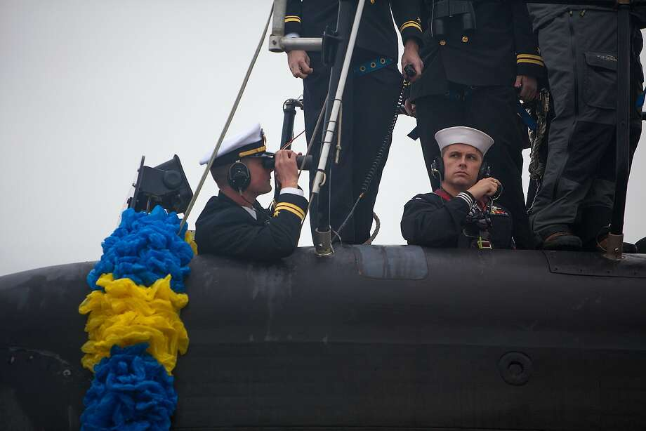 Sub story: Lt. Eli Heatherly (left) and Petty Officer 1st class Kevin Rooke communicate with submarine control while docking the USS Helena as it nears the pier of Norfolk Naval Station in Norfolk, Va. About 150 sailors returned home with the Helena after six months at sea. Photo: Hyunsoo Leo Kim, Associated Press