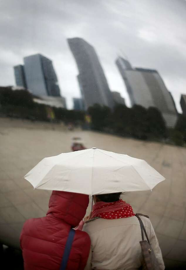 Rainy day perspective: Susan Pascual and Rina Hitofif reflect on the Cloud Gate sculpture in Chicago's Millennium Park. Photo: Charles Rex Arbogast, Associated Press