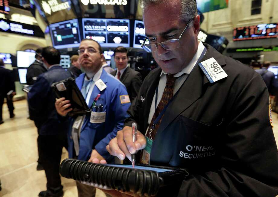 Trader Kenneth Polcari, right, works on the floor of the New York Stock Exchange Tuesday, Oct. 15, 2013.The stock market edged lower early Tuesday even though Republican and Democratic leaders in the Senate reported that a deal over the nation's borrowing limit appears to be getting closer. (AP Photo/Richard Drew) ORG XMIT: NYRD109 Photo: Richard Drew / AP