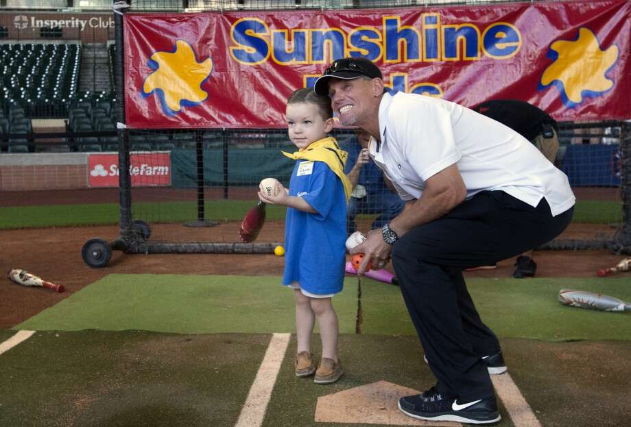 Max McMichael, 3, left, stands with former Astro Craig Biggio, right, as he tells him to look at the big screen during a Sunshine Kids Foundation event at Minute Maid Park on Tuesday. Kids and their families got the opportunity to hit pitches thrown by Biggio along with the opportunity to play at the ballpark. Photo: Cody Duty, Houston Chronicle