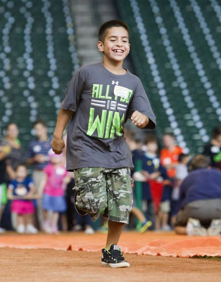 Aaron Vasquez, 9, runs the bases after hitting a baseball. Photo: Cody Duty, Houston Chronicle