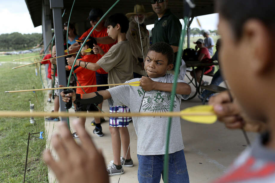 Malachi Coleman, 7 (center), learns how to use a bow and arrow on the archery range with his brother, Kanye Coleman, 9 (right), during New Scout Superhero Academy at the Castle Hills-area McGimsey Scout Park.