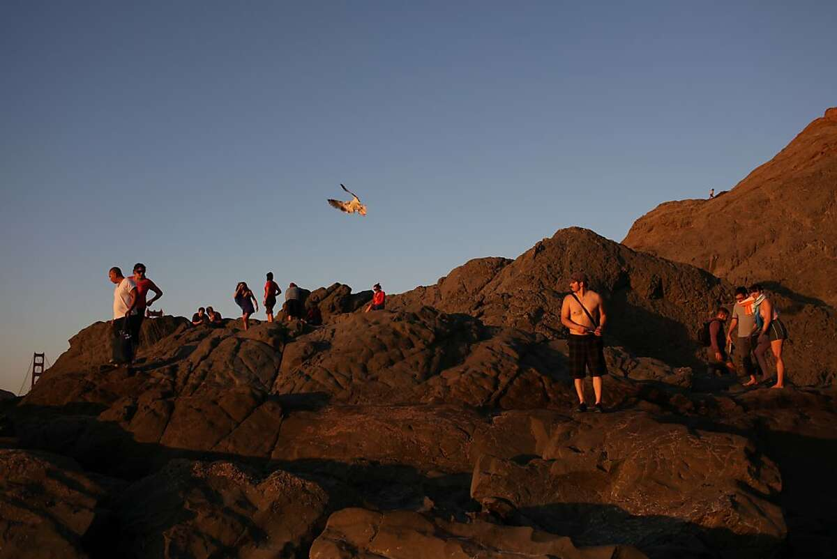 People watch the sunset at Baker Beach on October 5, 2013 in San Francisco, Calif.