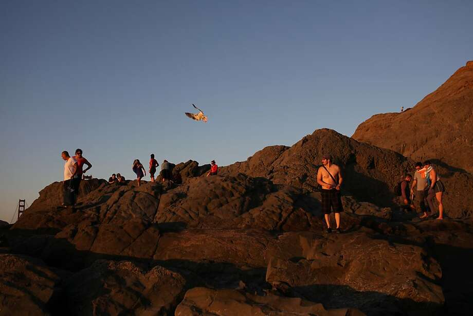 People watch the sunset at Baker Beach on October 5, 2013 in San Francisco, Calif. Photo: Pete Kiehart, The Chronicle