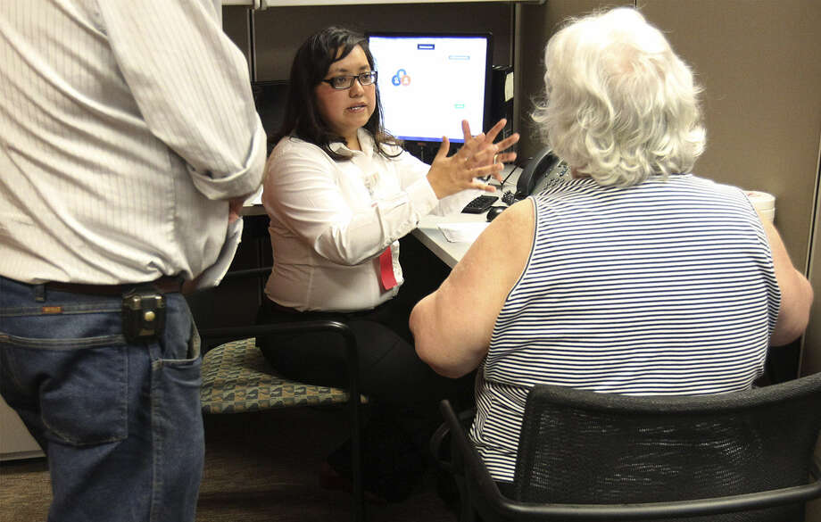 Certified Application Counselor Maria Lee (center) talks to a couple interested in enrolling in the Health Insurance Marketplace at CentroMed Wellness Center. Photo: Kin Man Hui / San Antonio Express-News