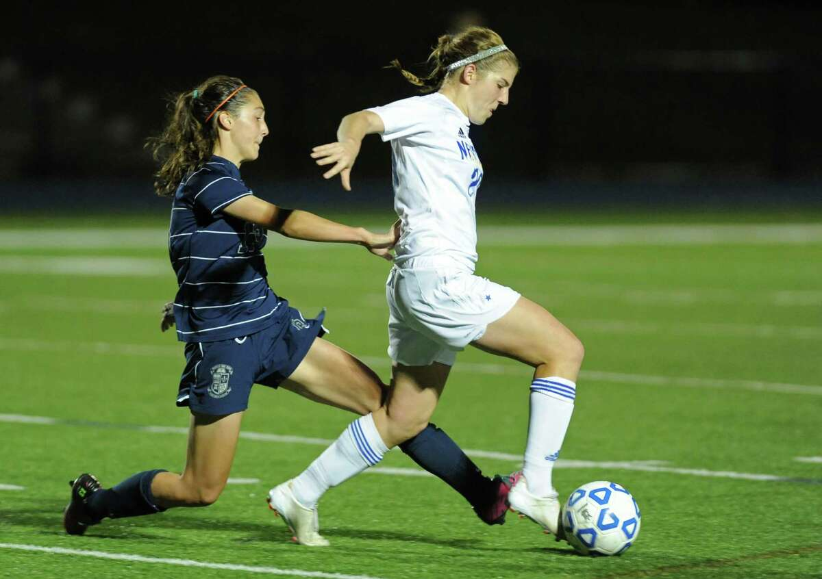 Immaculate's Paige Davis, left, battles Newtown's Anna Northrop for the ball in the SWC girls soccer match between Newtown and Immaculate at Newtown High School in Newtown, Conn. on Tuesday, Oct. 15, 2013.
