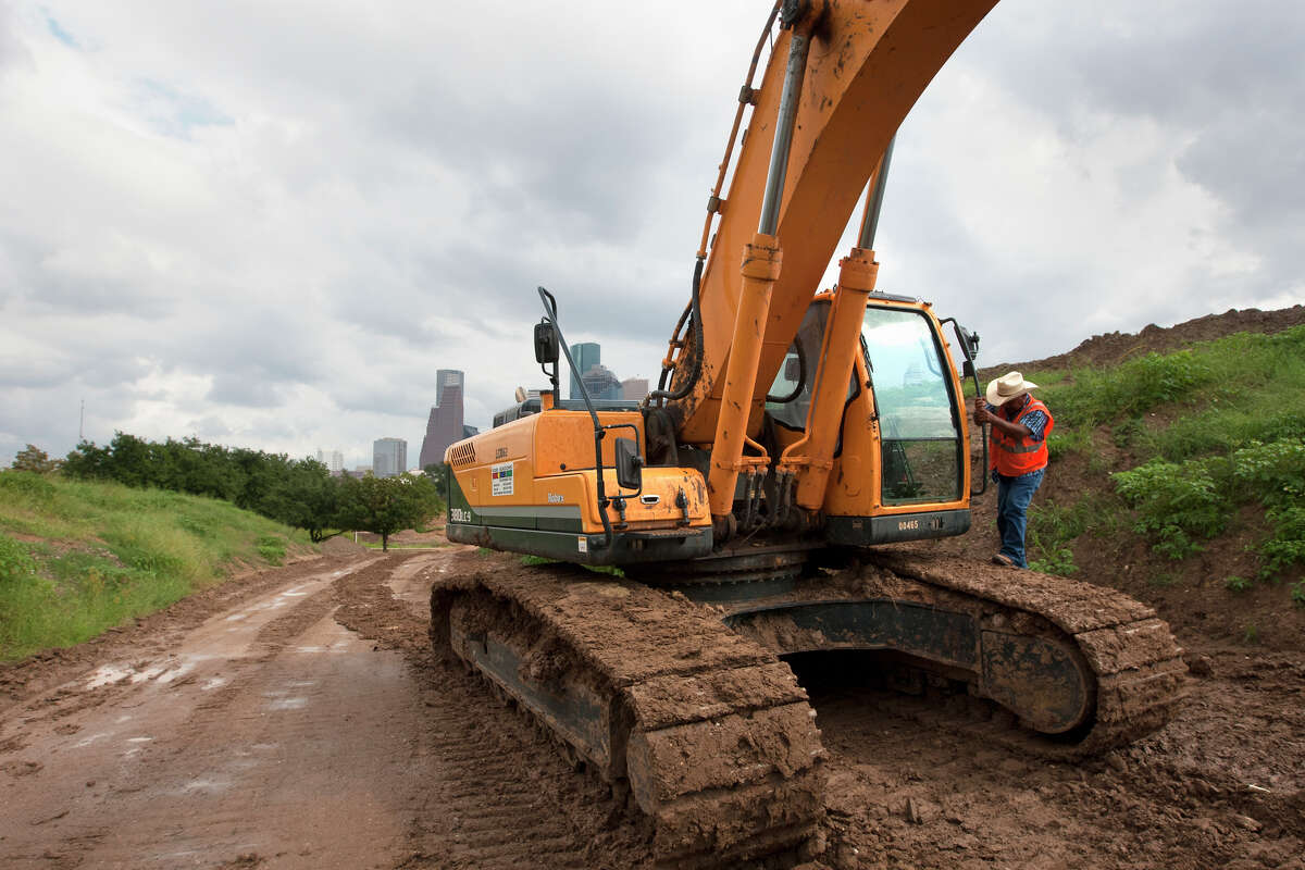 A construction crewman gets out of an excavator after working to transform Buffalo Bayou Park, Tuesday, Oct. 15, 2013, in Houston.
