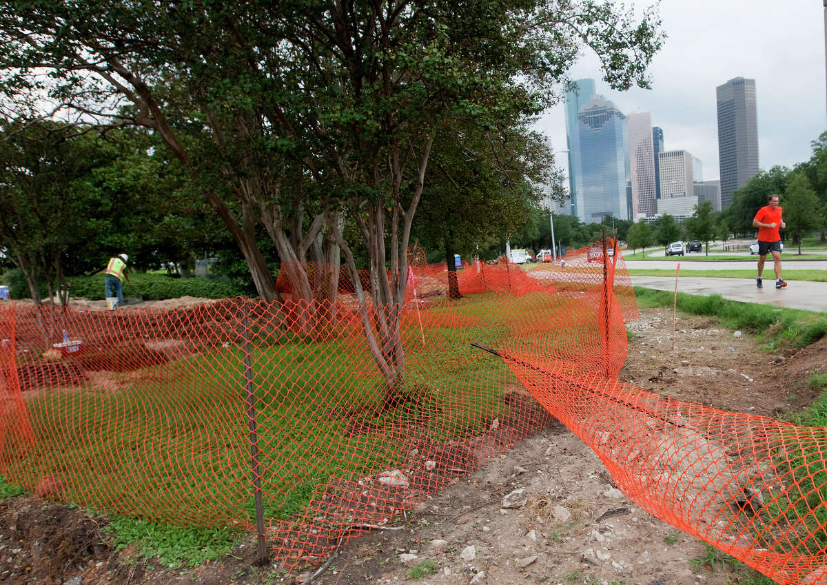 A jogger makes his way down a paved trail as a construction crew works to transform Buffalo Bayou Park, Tuesday, Oct. 15, 2013, in Houston.