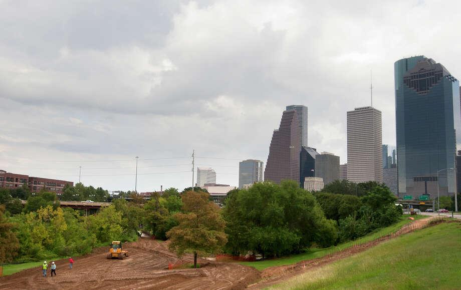 Construction crew members walk along Buffalo Bayou Park as they work to transform it, Tuesday, Oct. 15, 2013, in Houston. Photo: Cody Duty, Houston Chronicle / © 2013 Houston Chronicle