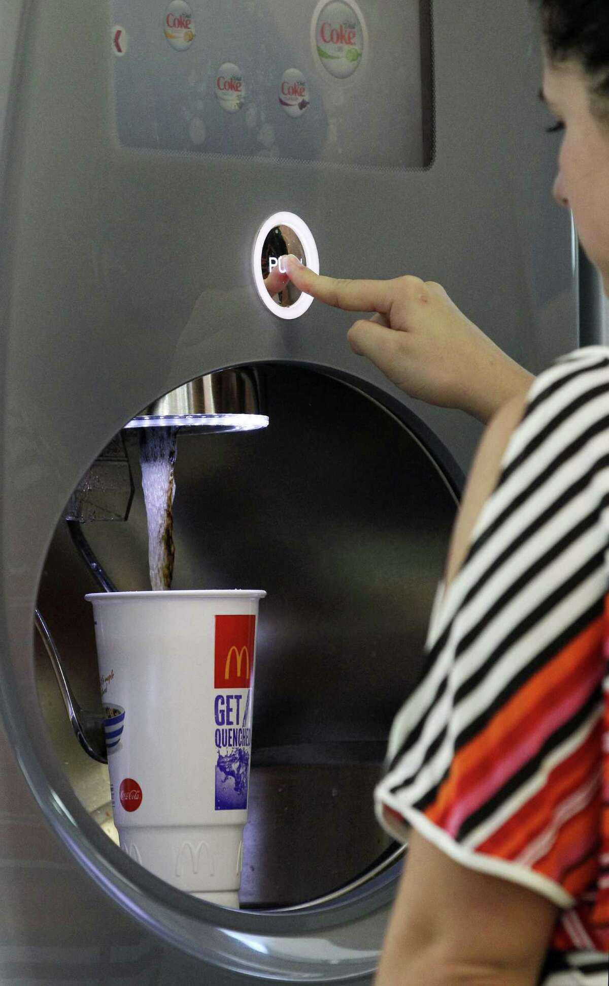 Christina Nunez fills a cup at a fast-food restaurant in New York. Nationally, more than half of front-line fast-food workers' families use at least one public assistance program.