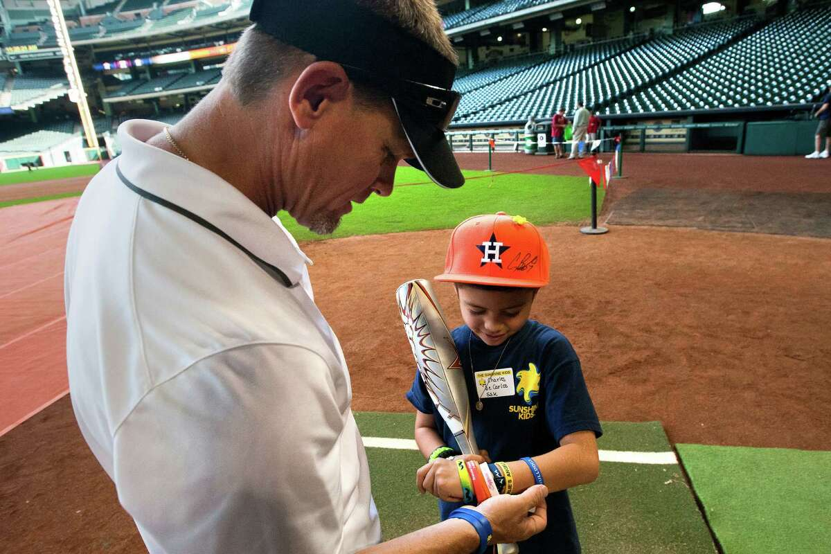 Former Astro Craig Biggio, left, compares bracelets with Charles De Carlos, 6, right during a Sunshine Kids Foundation event at Minute Maid Park, Tuesday, Oct. 15, 2013, in Houston. Sunshine Kids, dedicated to children with cancer, hosted the event to give kids and their families the opportunity to hit pitches thrown by Biggio along with the opportunity to play at the ballpark.