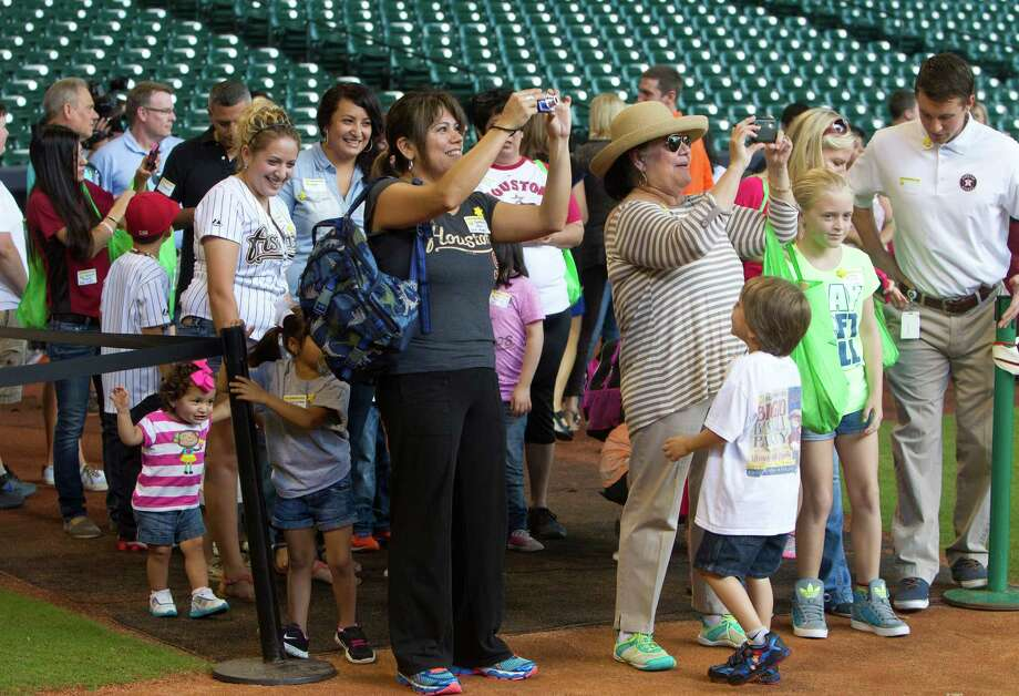 Friends and family take photos during a Sunshine Kids Foundation event at Minute Maid Park, Tuesday, Oct. 15, 2013, in Houston. Photo: Cody Duty, Houston Chronicle / © 2013 Houston Chronicle