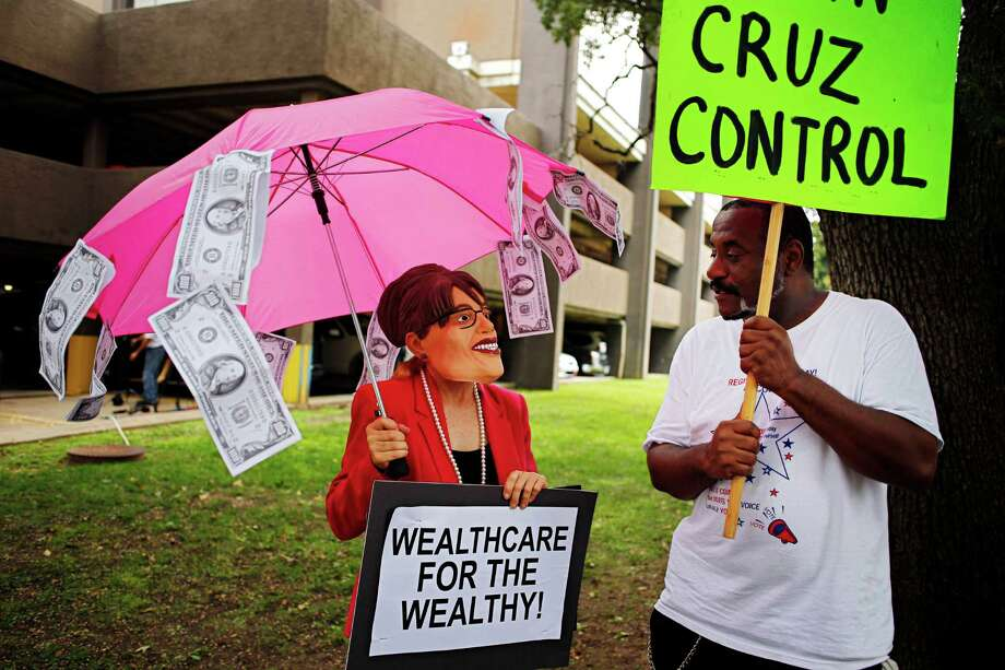 Leslie Harris, left, wears a Sarah Palin mask as she and Will Pritchett rally Tuesday against Sen. Ted Cruz outside his Dallas office. Photo: G.J. McCarthy, MBR / The Dallas Morning News