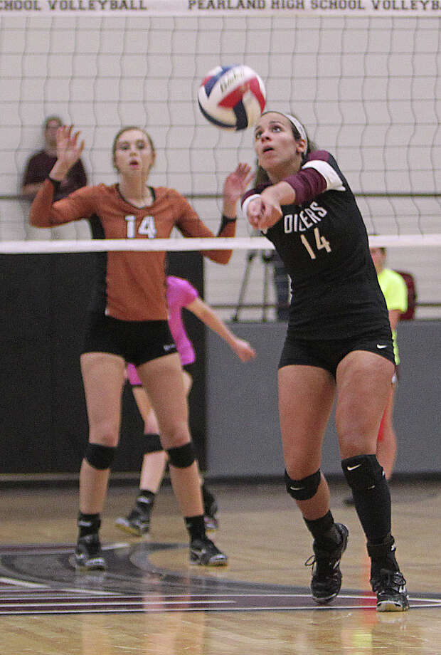 Pearland's Haley Morton right, hits the ball as Alvin's Madison Andrews left, looks on during high school volleyball game action at Pearland High School Tuesday, Oct. 15, 2013, in Pearland. Photo: James Nielsen, Houston Chronicle / © 2013  Houston Chronicle
